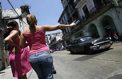 Fotografía de archivo de una mujer hace detener un auto de  época utilizado como taxi en La Habana